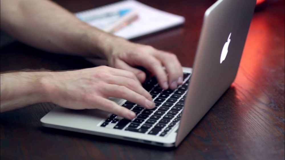 Man's Hands Typing On Macbook Keyboard